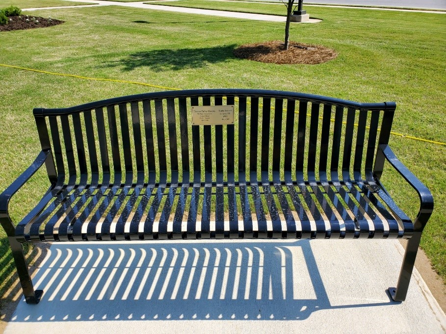 Picture of one of the five benches around the park that have a plague that remembers different Veterans that fought and died for our country.