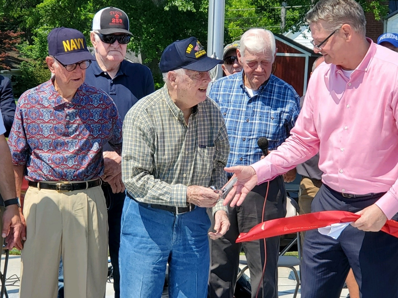 Picture of Veterans lined up for the Veterans Memorial Ribbon Cutting.Iwo Jima survivor Johnny Cantrell cutting the ribbon for the Veterans Memorial Park grand opening.